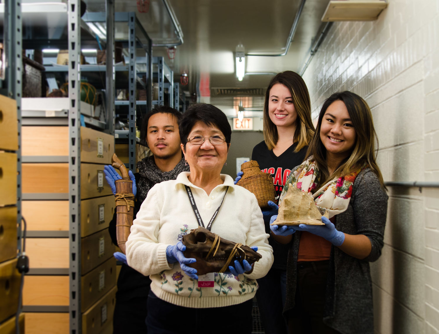 Image depicting volunteers Etta McKenna, Oscar Docto, Tess Madden, and Alpha Sadcopen posing with objects within CAS Mezzanine storeroom. Selected for use on the homepage of the Philippine Heritage Collections interactive web portal. (c) Field Museum of Natural History - CC BY-NC 4.0