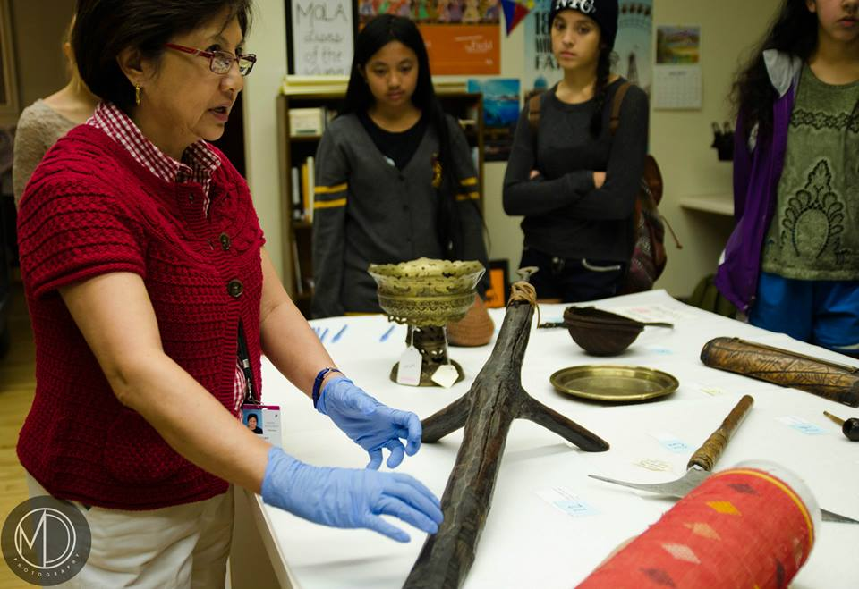 Image depicting volunteer Lani Chan describing how a coconut scraper is used to visiting group from Pittsburgh's YFAP. Selected for use on the homepage of the Philippine Heritage Collections interactive web portal. [Copyright] Field Museum of Natural History - CC BY-NC