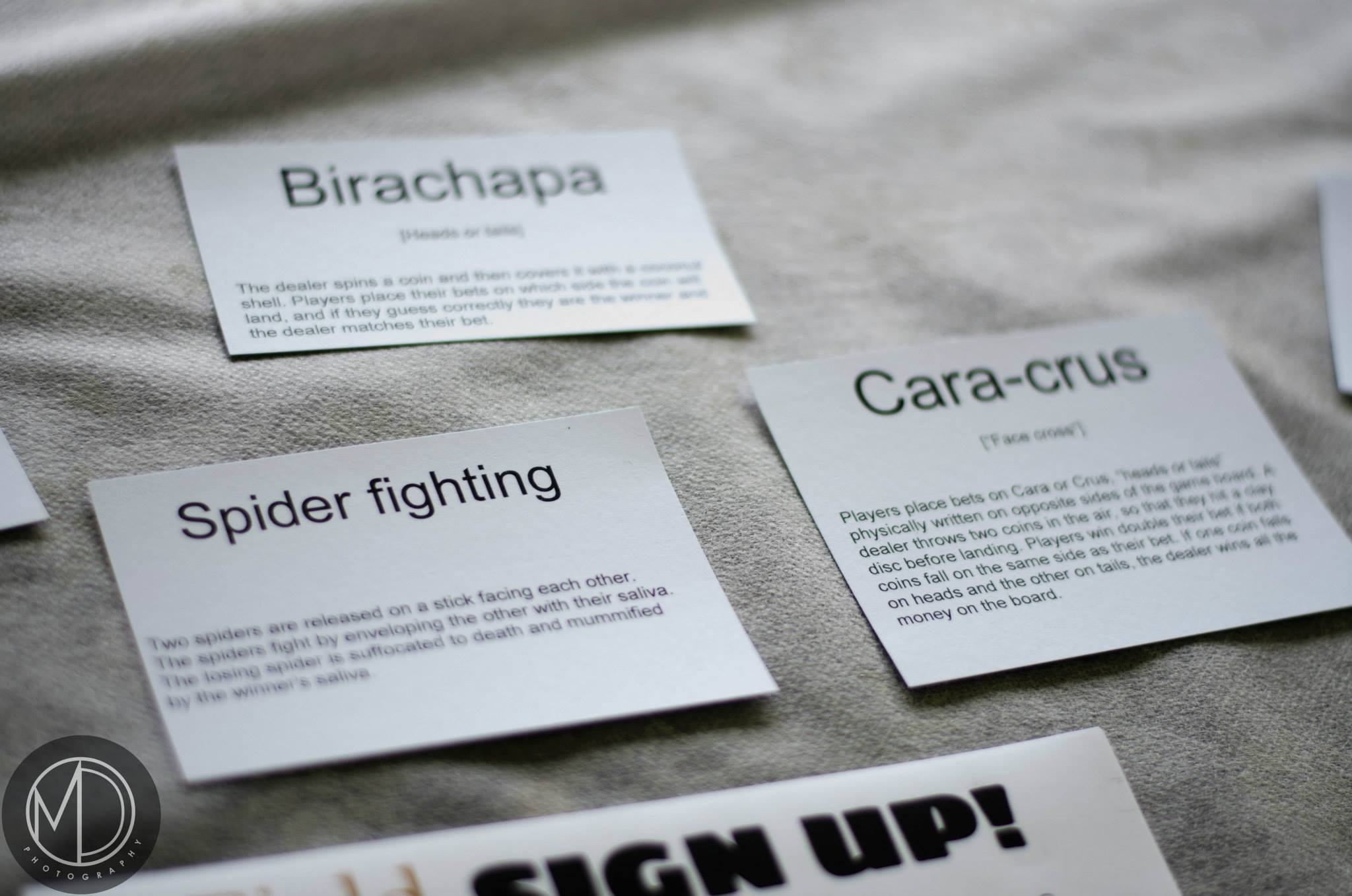 Close up of cards describing traditional Filipino games on The Field Museum's table in the Cultural tent.
