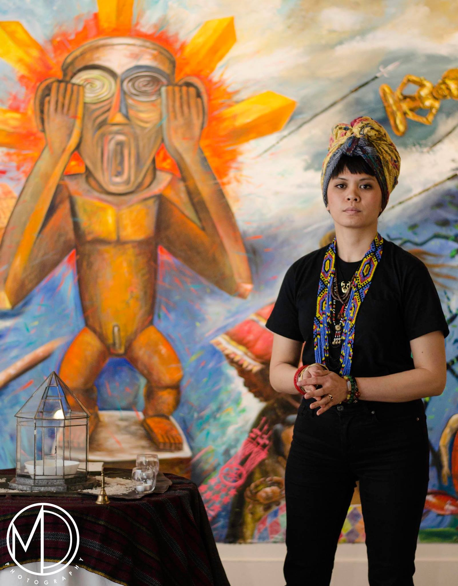 Volunteer standing next to altar for the bulol in the mural.