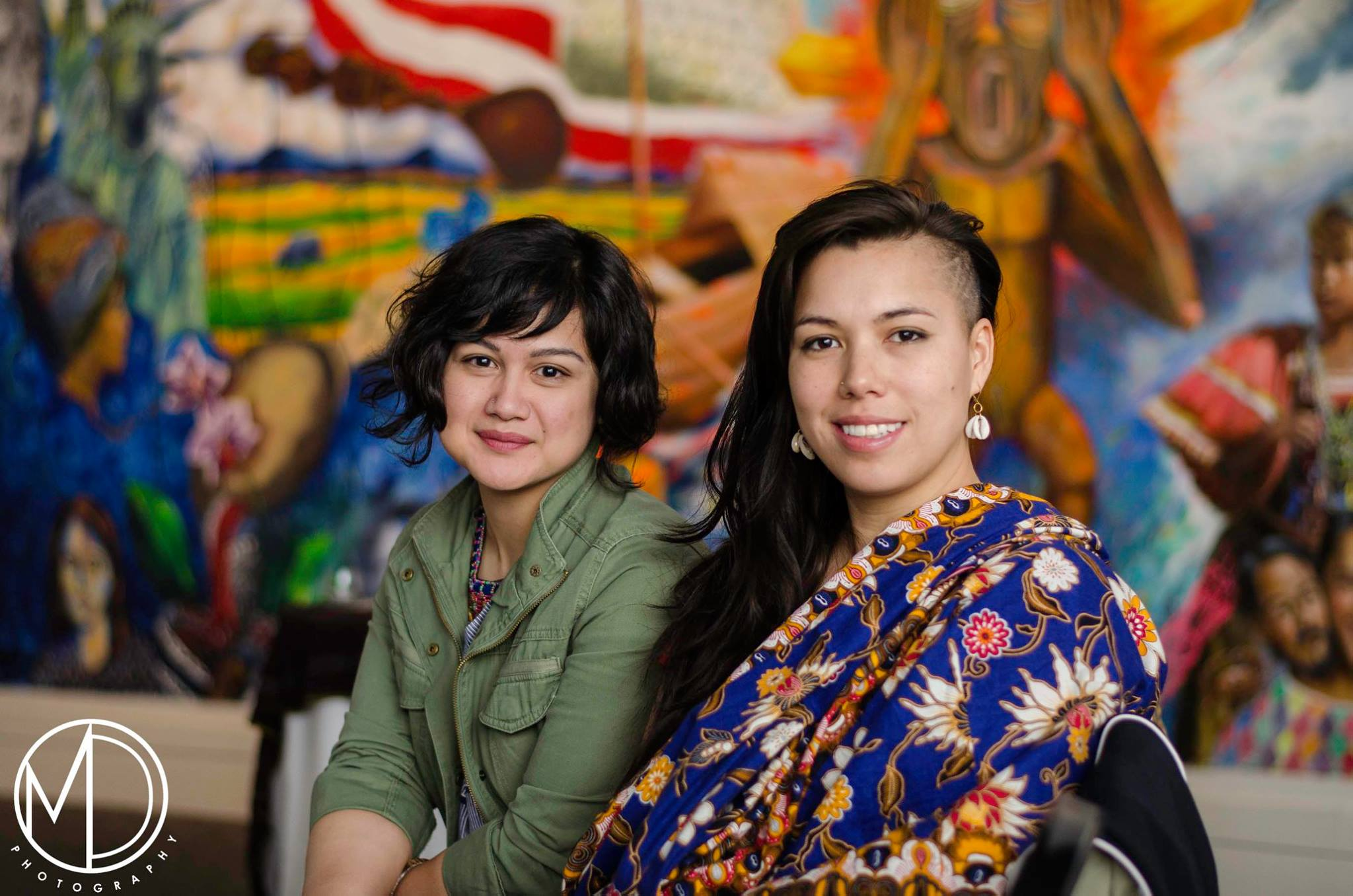 Two women seated in front of mural.