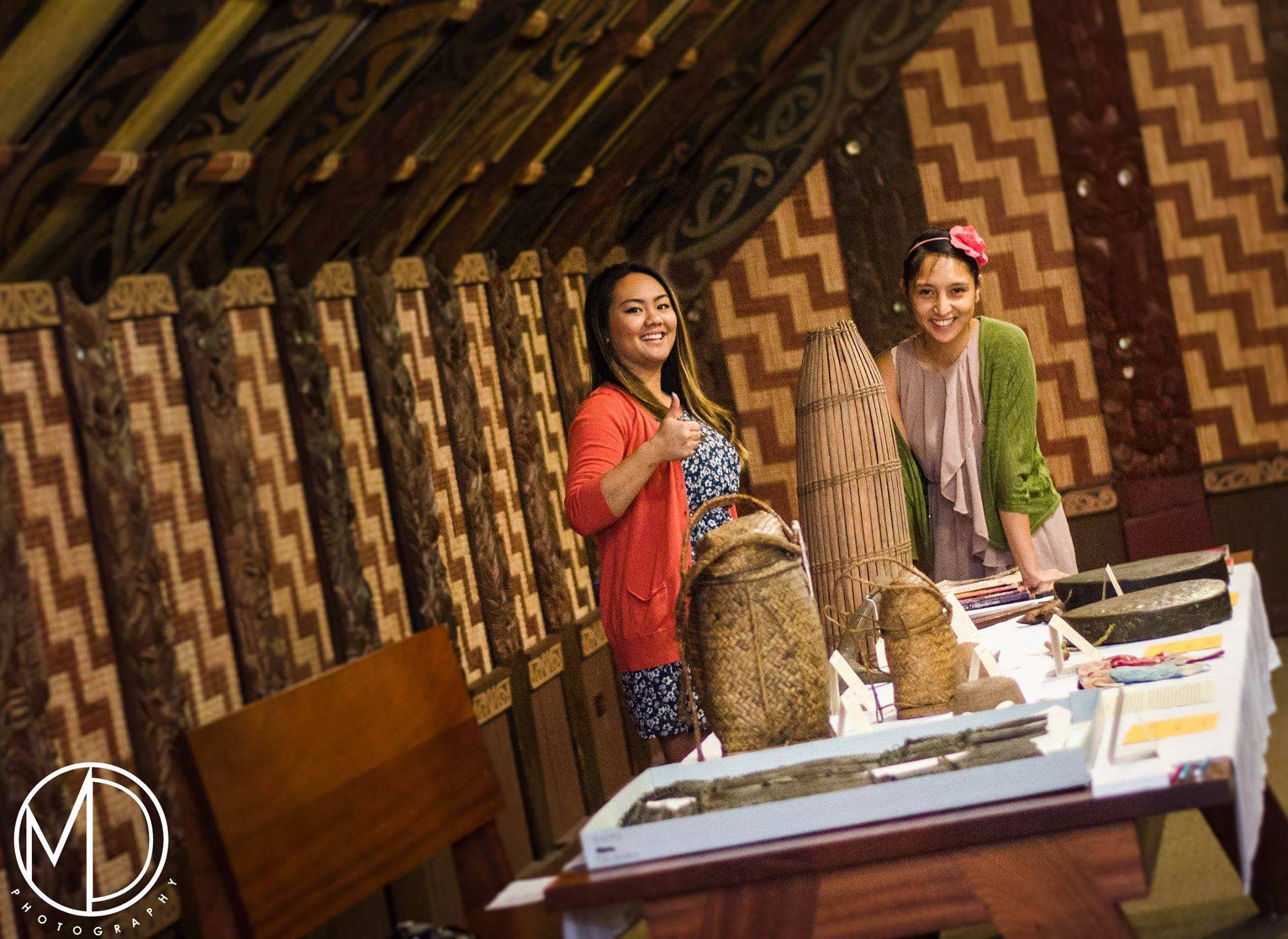 Volunteers posing next to tables of artifacts on display inside the Maori House.