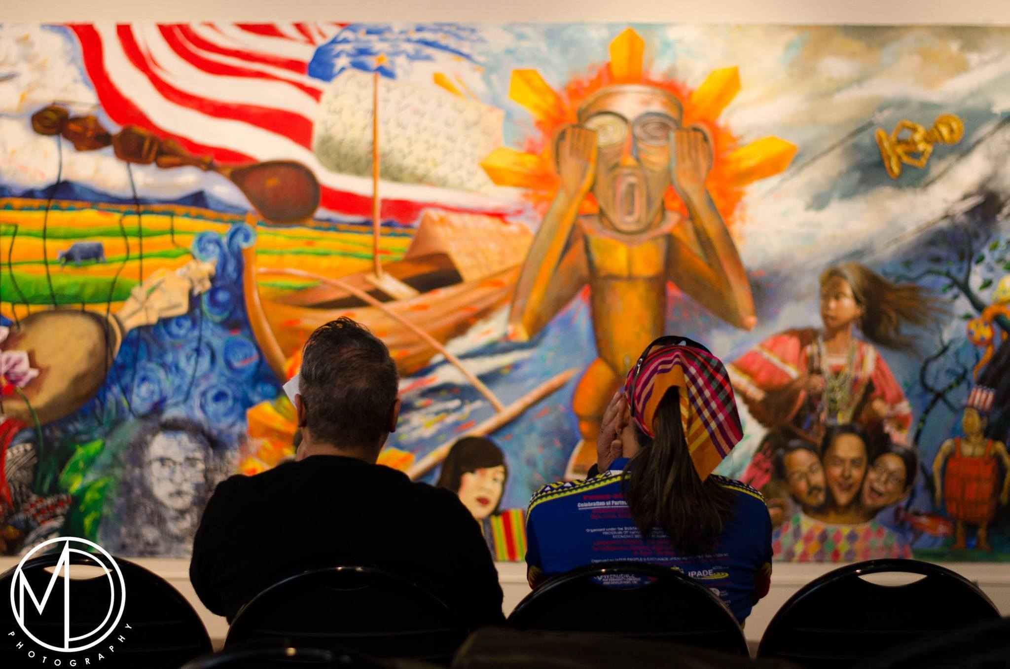 Guests Cesar Conde and Levi Aliposa viewing the Art and Anthropology collaborative mural.