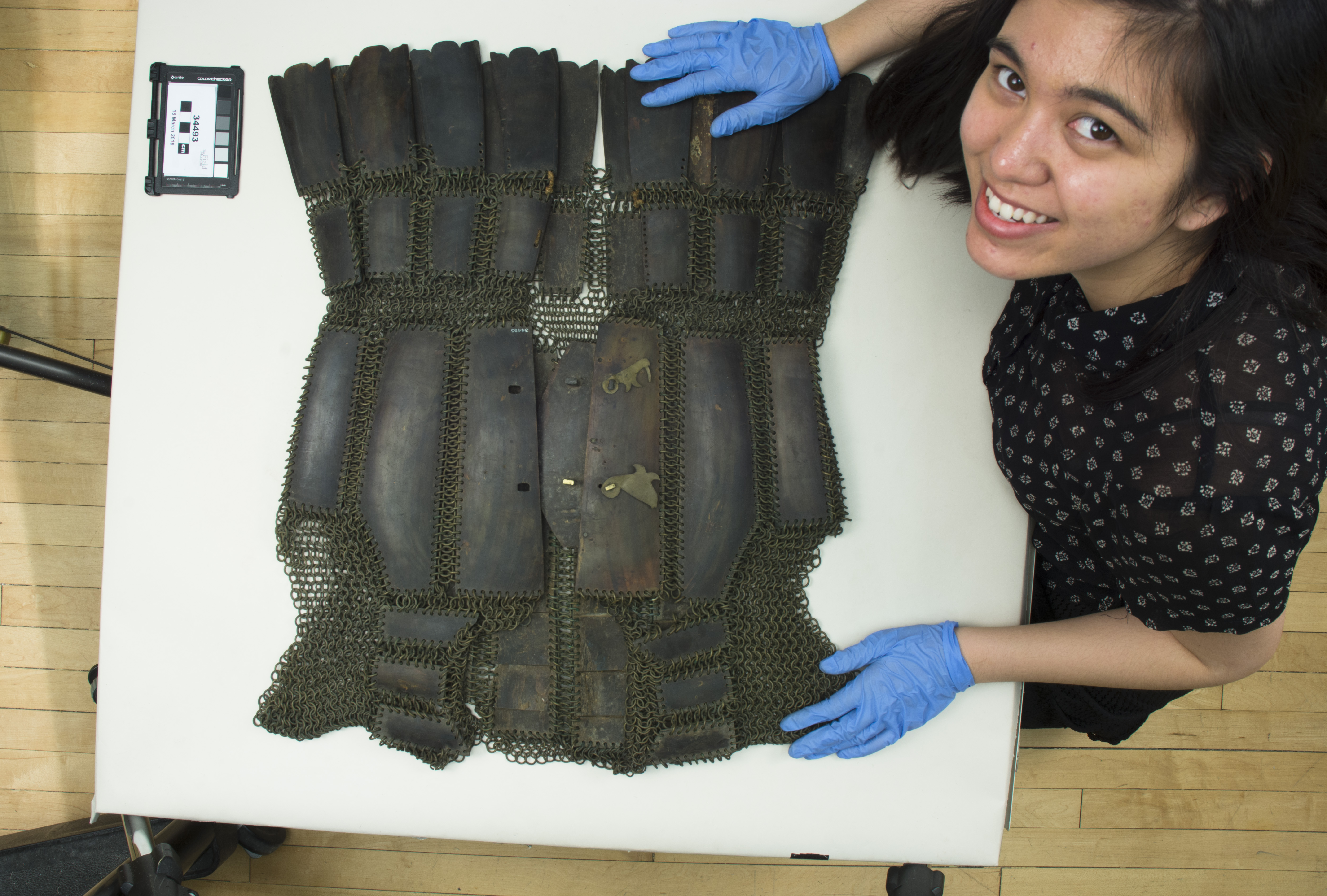 Loren photographing a suit of carabao horn armor. [Copyright] Field Museum of Natural History - CC BY-NC