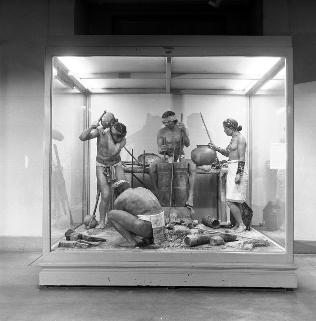 Tinguian Iron Workers. Life Size diorama museum exhibit in glass case. Based on Forge from Balbalasang Philippine Islands. 3 men, 1 woman figures. Models made by Clyde Gardner. Hall E Philippines. Exhibit case 22. Documentary record before deinstallation [Copyright] Field Museum of Natural History - CC BY-NC