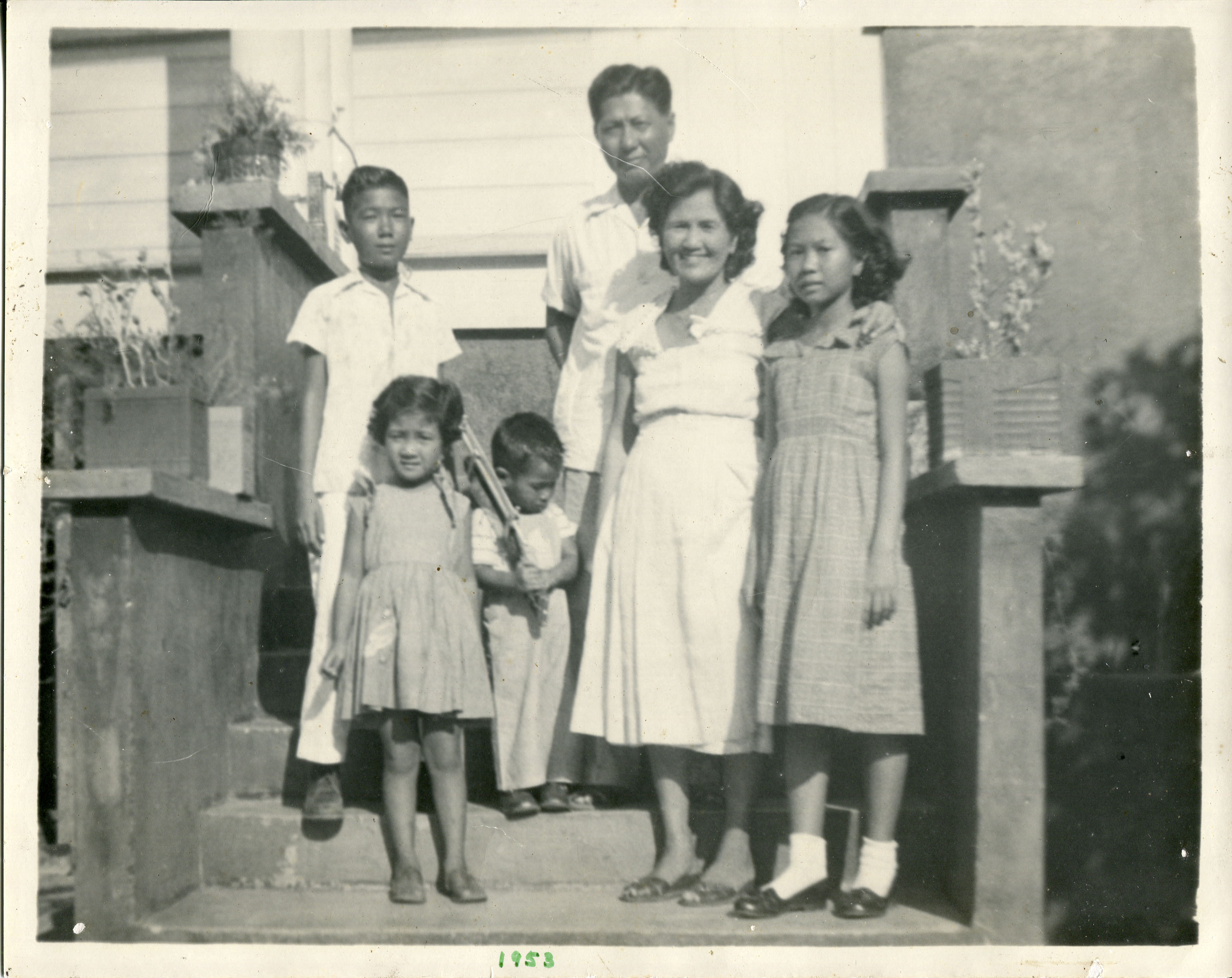 "Family photo 1953 owned by Etta McKenna. 1953 photo of family standing on the steps in front of our old house. Parents: Hermogenes Escarrilla (father) and mother Felicula Escarrilla. Brothers Efrain, Ernie. Sister Edna  Notes from Sarah Carlson, in discussion with McKenna: ""Important to me because this is the only copy saved as all photos were destroyed due to termite infestation. That is why I want this digitized. Also makes me reminisce of all the things I did growing up in the house.   Any views, findings, conclusions, or recommendations expressed in this story do not necessarily represent those of the National Endowment for the Humanities. [Copyright] Field Museum of Natural History - CC BY-NC"