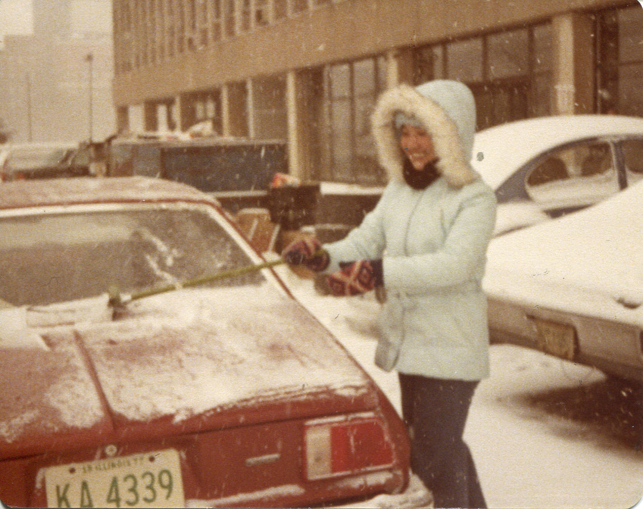 "Photo of Etta McKenna, 1977. Taken in Jan 1978 in the parking lot of 1926 W Harrison. First snow in Chicago winter '78,  Taken by ""my friend, Agnes Clement, while cleaning her car.""  Pictured: ""myself cleaning the car"" [One woman in cleaning snow off a car]  Notes from Sarah Carlson, in discussion with McKenna: ""This reminds me of my first snow in Chicago. I was wearing a parka bought from Woolworth's on sale. It was a thin parka so one of the first experiences in the cold. Not since I came to Chicago had I felt how cold is 'cold'! Cleaning my friend's car, a Chevy Monza.   Any views, findings, conclusions, or recommendations expressed in this story do not necessarily represent those of the National Endowment for the Humanities. [Copyright] Field Museum of Natural History - CC BY-NC"
