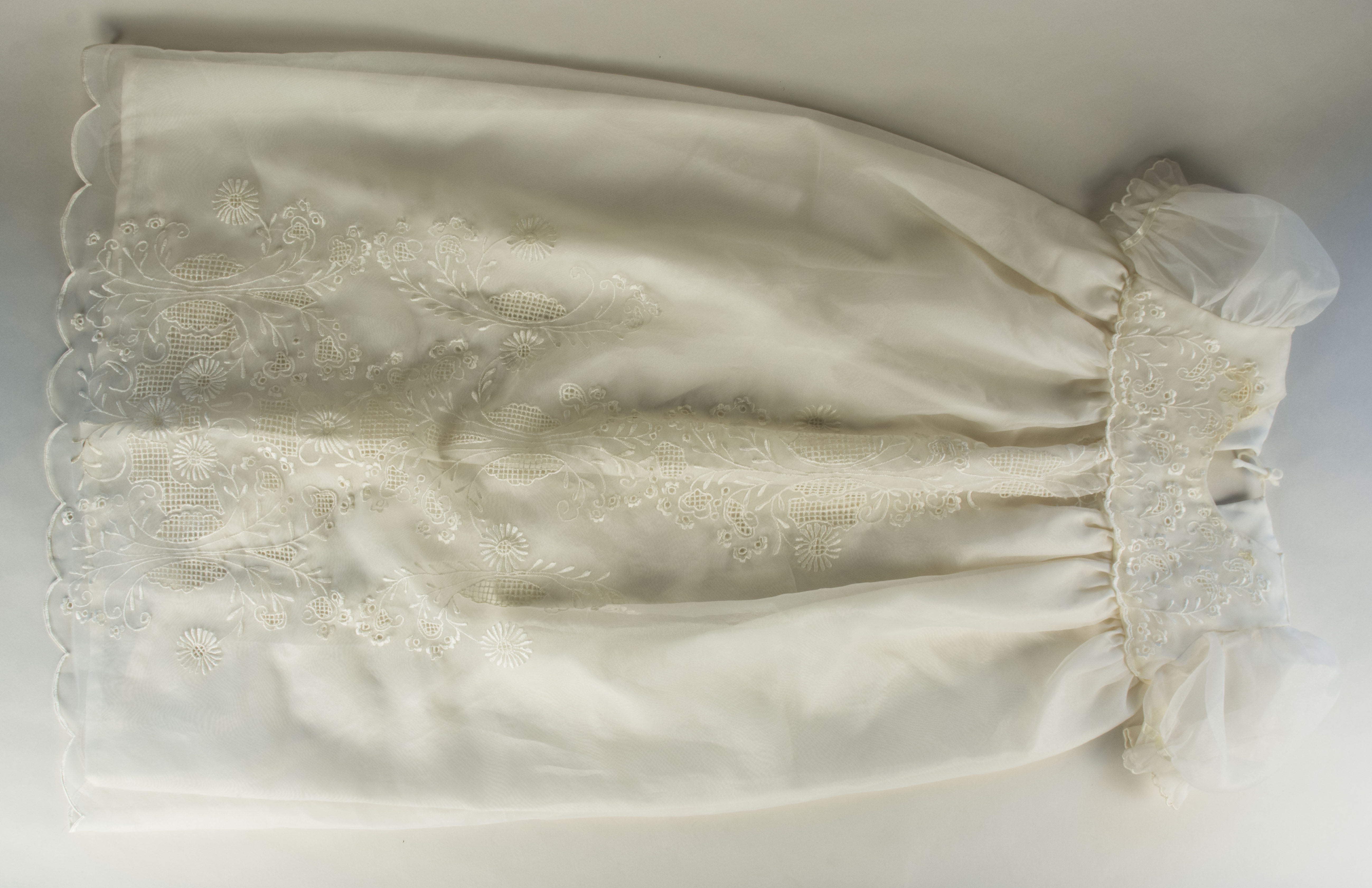 Baptism gown owned by Claudia Jamilla- front view Daughter's baptismal gown from 1997. Claudia  noted that this was probably made in southern Luzon. It was a gift from mother-in-law [the mother of Claudia's husband; Stephanie's grandfather. Symbolizes daughter's [Stephanie's] birth.   Any views, findings, conclusions, or recommendations expressed in this story do not necessarily represent those of the National Endowment for the Humanities. [Copyright] Field Museum of Natural History - CC BY-NC
