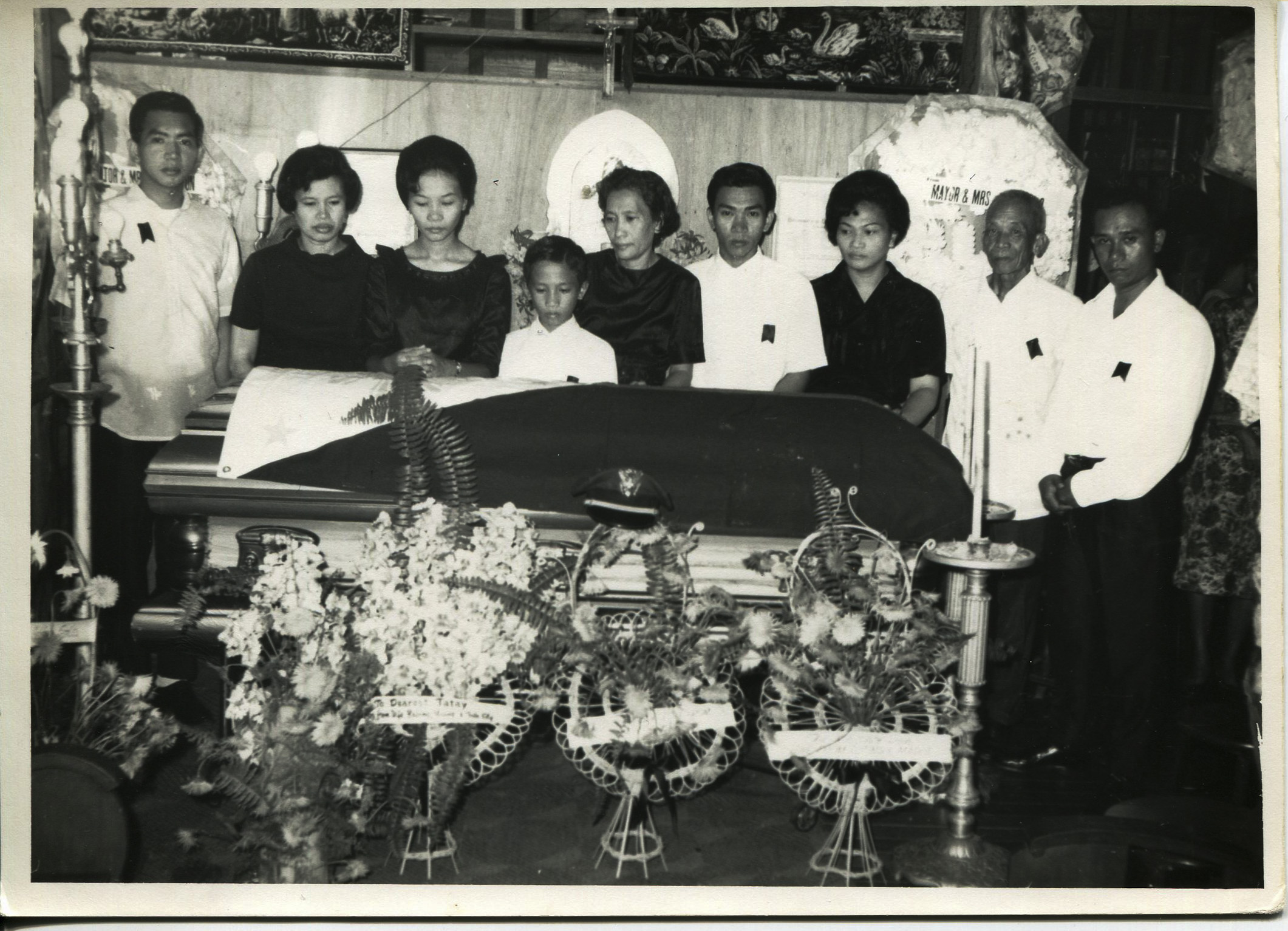 """Photo of Arguelles' family, October 13, 1967.  Arguelles acquired the photo in 2011 when her dad died. It was taken at Jaro Cathedral in Iloilo City at Arguelles' grandfather's funeral. The grandfather was a policeman and his funeral was very impressive with salutes and tributes. Left to right: Pedro (uncle), Magdalena (mother), Isabel (aunt), Eliseo (uncle), """"Noning"""" Dionisia (step grandmother), Ismael (uncle), Amparo (aunt), unknown, father """"Toting"""" Jose. Arguelles likes that this picture shows how important Catholicism has been to her family, and how well loved her grandfather was.   Any views, findings, conclusions, or recommendations expressed in this story do not necessarily represent those of the National Endowment for the Humanities. (c) Field Museum of Natural History - CC BY-NC 4.0"""