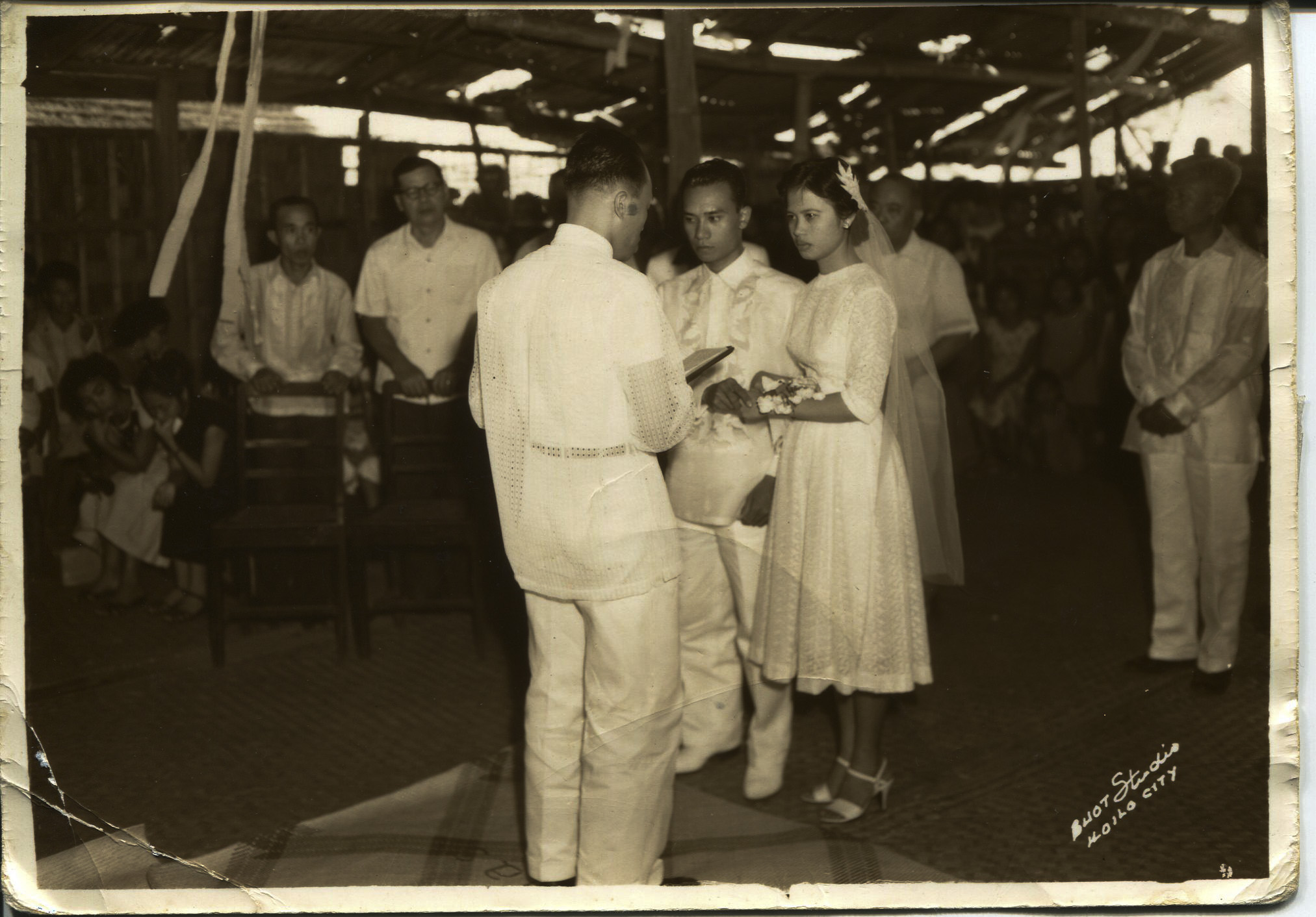 "Photo of Arguelles' parents' wedding, 1958. Arguelles acquired it in 2011 after her dad died. The photo was taken on Nasidman Island, Iloilo at Arguelles' parent's wedding. The wedding took place in Aglipay Church, which was an Indigenous religion mixed with Catholicism. Text on the photo says: ""Buot Studio Iloilo City"". Pictured: Pastor, Jose Arguelles (dad ""Tay""), Magdalena (mom ""Nay""), Pedro B Molina (maternal grandfather, mayor of Ajuy). Arguelles' mom was an oldest child. She was the first nurse in her family and sent all her siblings to school. Arguelles' dad was a second child and also sent all his siblings to school. Arguelles said her parents coming together is symbolic of the future of the Philippines at that time. Her parent's generation is still very involved in the Philippines. Hundreds of people like them helped others, though they themselves came from nothing.   Any views, findings, conclusions, or recommendations expressed in this story do not necessarily represent those of the National Endowment for the Humanities. [Copyright] Field Museum of Natural History - CC BY-NC"
