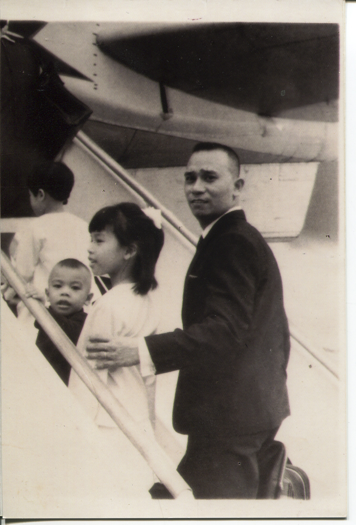 "Photo of Arguelles and family, 1969.  This is a newer copy (one of many) which Arguelles acquired in 2008 from an aunt. The photo was taken at the Manila airport and Arguelles said it could be a TWA airplane to Canada. Left to right: back of mother (Magdalena- holding Gene [brother] not pictured), Magdalena (self), Lester (brother), Althea (sister), Jose (father). Written on the back is: ""MIA June 16, 1969 They go afar off with the faith of Abram but shall come back with the thoughts and feelings of Jacob. -P Molina. He looked back to explain his sad thoughts. ""To Morit and Toting""  Arguelles said the photo was important because it represents a total break from the country she had known until age 6. She said leaving broke her whole idea of the world and that she understood the world was bigger. Arguelles had to be tutored in English and got new clothes. For her parents (dad was 40), Arguelles said there were far better economic opportunities. Both parents had siblings who were nurses in Canada. Arguelles' parent's siblings helped them in Canada and it was an exciting time. Arguelles said that excitement wore off, leaving the difficulties and prejudices of a new country.   Any views, findings, conclusions, or recommendations expressed in this story do not necessarily represent those of the National Endowment for the Humanities. [Copyright] Field Museum of Natural History - CC BY-NC"