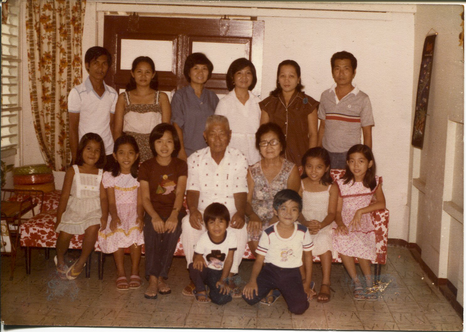"""Photo of Escarilla-Carnate and family, 1980 Taken in January 1980 in Iloilo City, in paternal grandparents' house by a professional photographer. Pictured are the grandparents, children, and grandchildren except 2 of her siblings who were born later. Escarilla-Carnate says the family speaks English and Tagalog, and the Ilongot dialect called Hiligaynon which has a """"melodious"""" tone compared to Karay-a which is """"harsh/harder"""" in tone.  Escarilla-Carnate said, """"This photo is significant because family is important and I am very close with siblings and cousins. Every Sunday, we have lunch or dinner with grandparents. These are good memories. Every Sunday after mass, my dad or or grandpa would stop by market to buy fresh meat, thin pork chops (no vegetables). Only one piece of liver was delivered on Sundays. There was no supermarket. We used vinegar and chili dip. The menu was always the same every Sunday.""""   Any views, findings, conclusions, or recommendations expressed in this story do not necessarily represent those of the National Endowment for the Humanities. [Copyright] Field Museum of Natural History - CC BY-NC"""