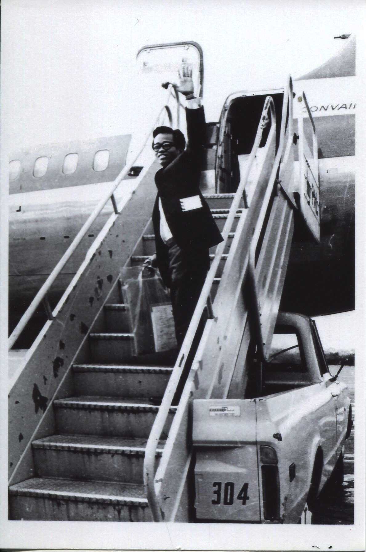Photo of Carnate, 1971 Taken in 1971 at the airport. Photographers at the airport took the photo and sold to his wife while they were saying goodbye. It was common for photographers to take emigration photos to sell to families. Pictured is Orlando waving from the plane as he leaves Manila.   Any views, findings, conclusions, or recommendations expressed in this story do not necessarily represent those of the National Endowment for the Humanities. [Copyright] Field Museum of Natural History - CC BY-NC