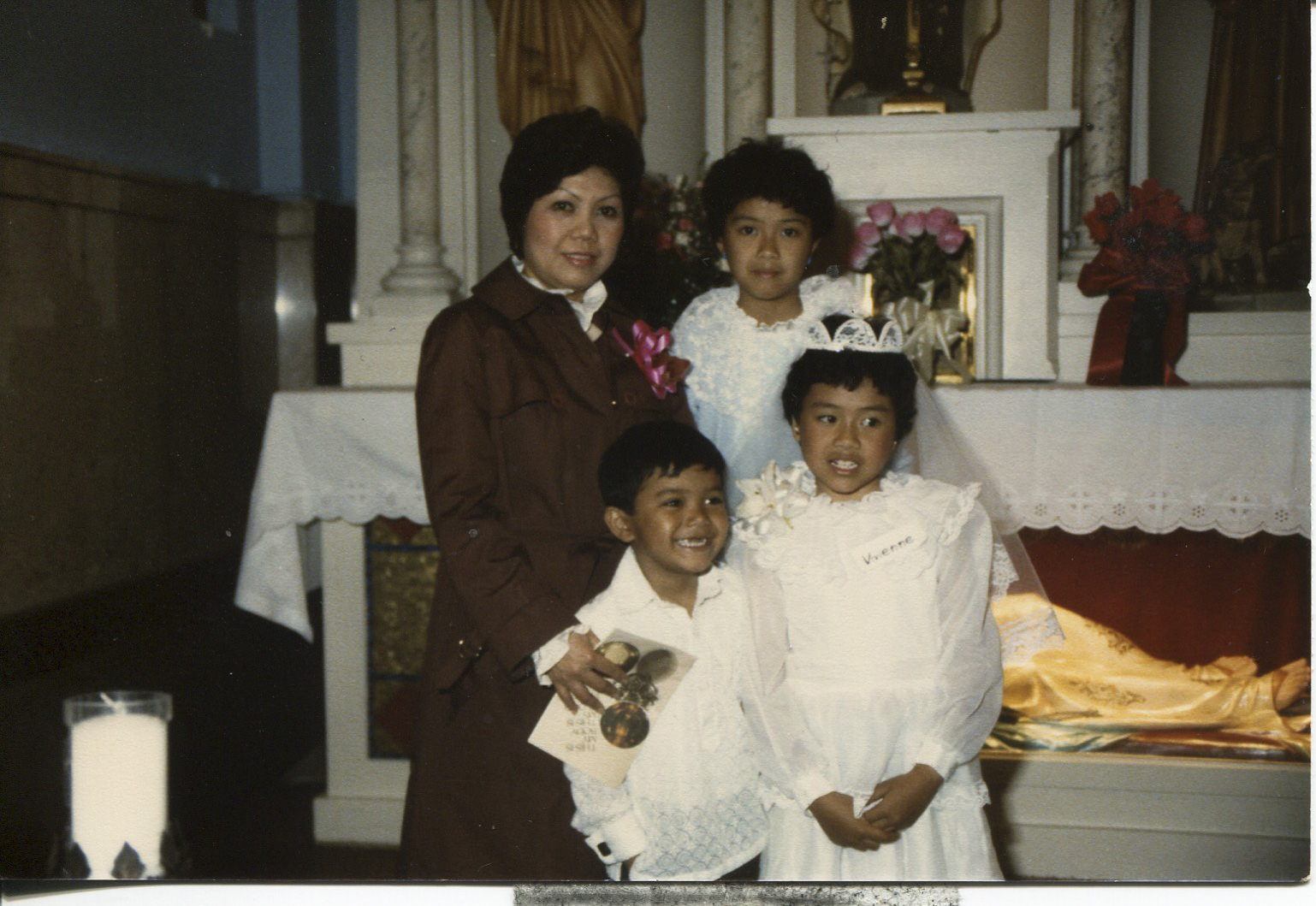 """Photo of Tan's family, 1987  Taken in Chicago at Our Lady of Pompeii Church, Lexington. The back of the photo says """"Please return to Necitas D. Tan class of 1963"""". Pictured: back row L-R: Necitas, daughter Simonette. Back row: son Jason, daughter Vivienne. Tan said the photo, """"shows the beginning of my life."""" Tan said the photo shows her family and represents the transition from being single to being married with a family in America. Tan's husband (Cesary Tan) is taking the photo. Tan is an orphan; her father died in WWII. She took an exam and passed it to get into school. All Tan's children are grown. Her daughter is married and has two kids in San Diego. Tan's daughter Simonette is the manager of an investment company. Her daughter Vivienne is a graphic designer. Her son Jason an electronic engineer.   Any views, findings, conclusions, or recommendations expressed in this story do not necessarily represent those of the National Endowment for the Humanities. [Copyright] Field Museum of Natural History - CC BY-NC"""