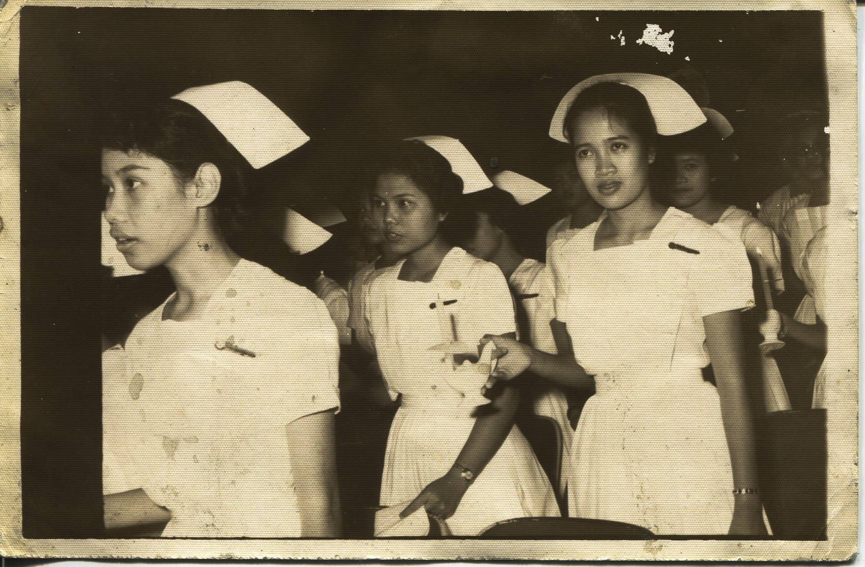 """Photo of Tan's graduation, 1963 - front Taken in 1963 at a graduation from Florence Nightingale at Philippine General Hospital. The back says """"Please return to Necitas D. Tan class of 1963"""". The photo shows Agnes Bandon (a friend of Tan's - Bandon is her maiden name); Necitas; and Gaying Dime (a friend of Tan's). Tan said, """"My life started. I was meant to be a nurse"""". Tan started school majoring in chemical engineering.   Any views, findings, conclusions, or recommendations expressed in this story do not necessarily represent those of the National Endowment for the Humanities. [Copyright] Field Museum of Natural History - CC BY-NC"""