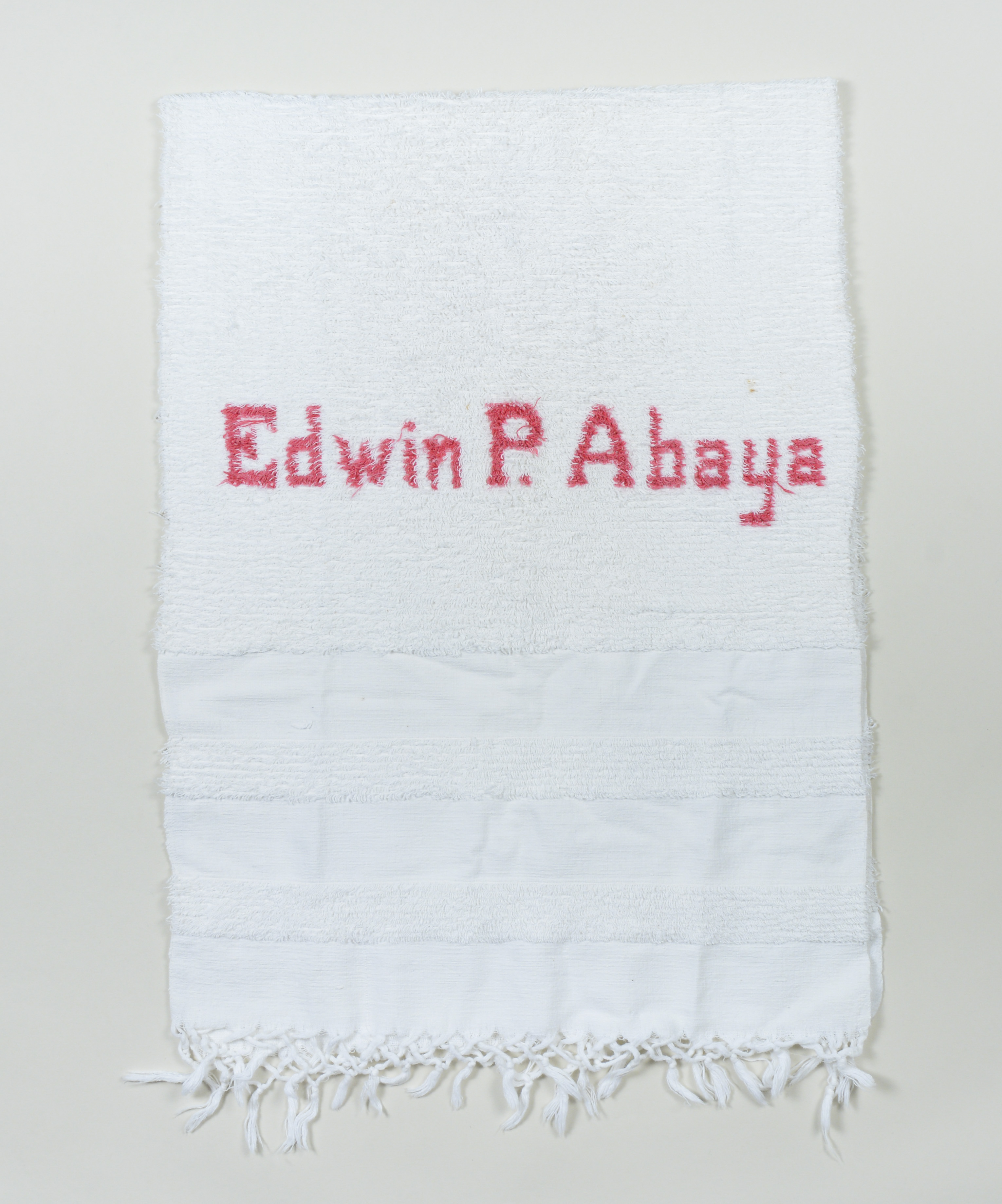 "Abel Iloko (Hand woven) bath robe owned by Edwin P. Abaya. Made in the early to mid 1960s; given to Edwin by his mother in the mid 1960s. He left the Philippines in 1968 and brought this towel with him because his mother had passed away by then and it is a keepsake from her. It was the only monogrammed object he had, and he likes that it looks like such quality work and they ""didn't misspell my name."" Vigan, Ilocos Sur, was known for hand weaving; they make clothing, towels, pashminas, etc. still today.   Any views, findings, conclusions, or recommendations expressed in this story do not necessarily represent those of the National Endowment for the Humanities. [Copyright] Field Museum of Natural History - CC BY-NC"