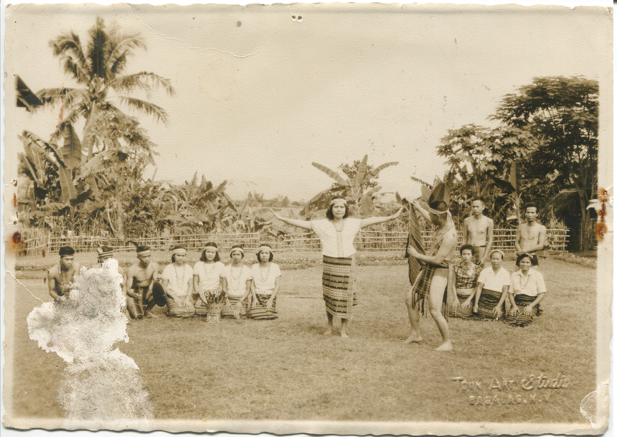"""Photo of man and woman dancing, surrounded by other seated dancers. This photograph was taken sometime before 1970 and acquired around 2000 from family, after grandmother passed away. Made in Bagabag, Nueva Vizcaya, Luzon. A woman and man are pictured dancing, surrounded by other people kneeling to watch them dance or take part in the dance. Embossed Text: """"Bagabag NV, Town Air Studio"""". Reminds Surla of family, grandmother's pride in her hometown, shows strength and presence.   Any views, findings, conclusions, or recommendations expressed in this story do not necessarily represent those of the National Endowment for the Humanities. [Copyright] Field Museum of Natural History - CC BY-NC"""