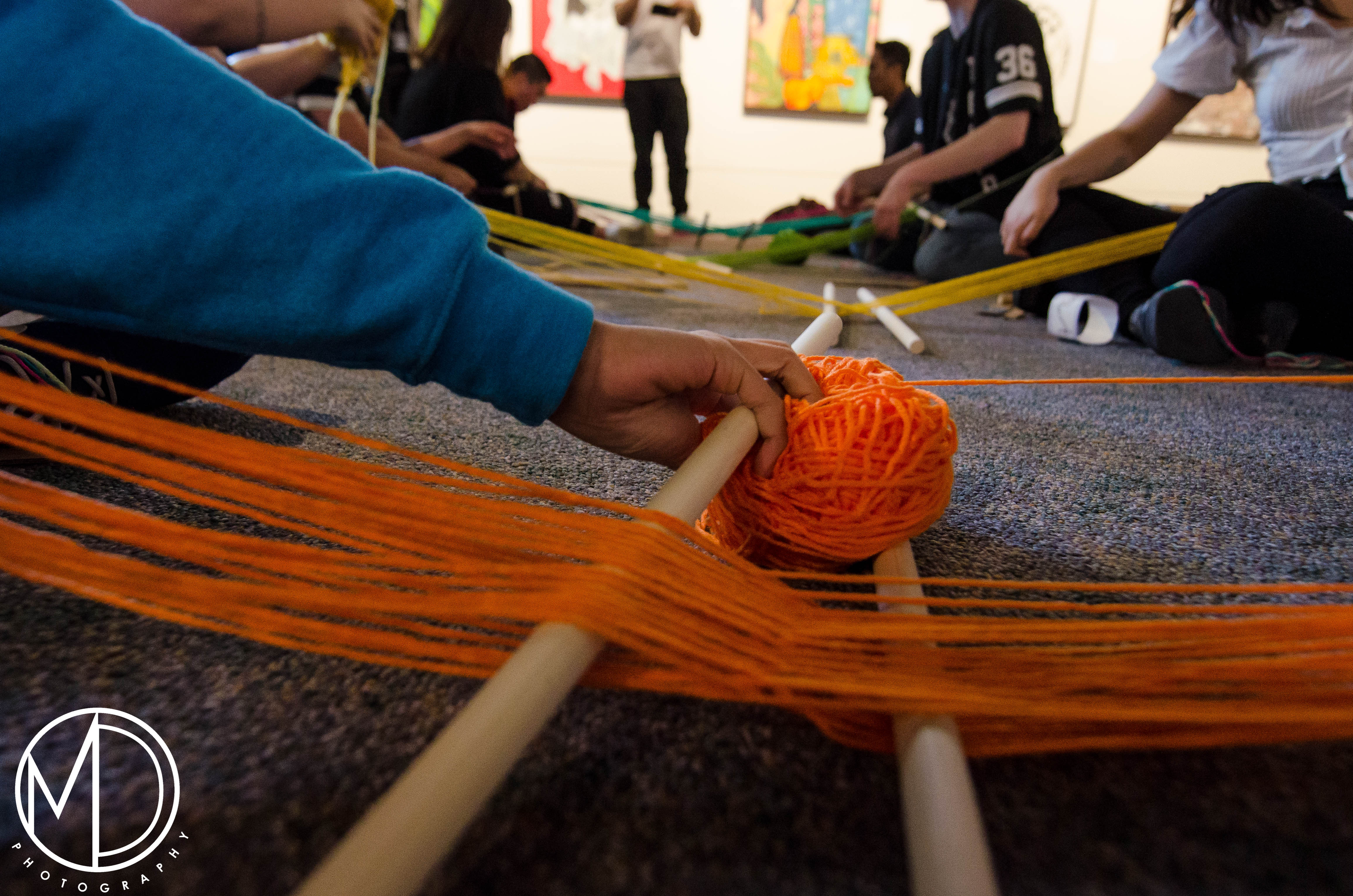 Guests participating in the weaving activity.