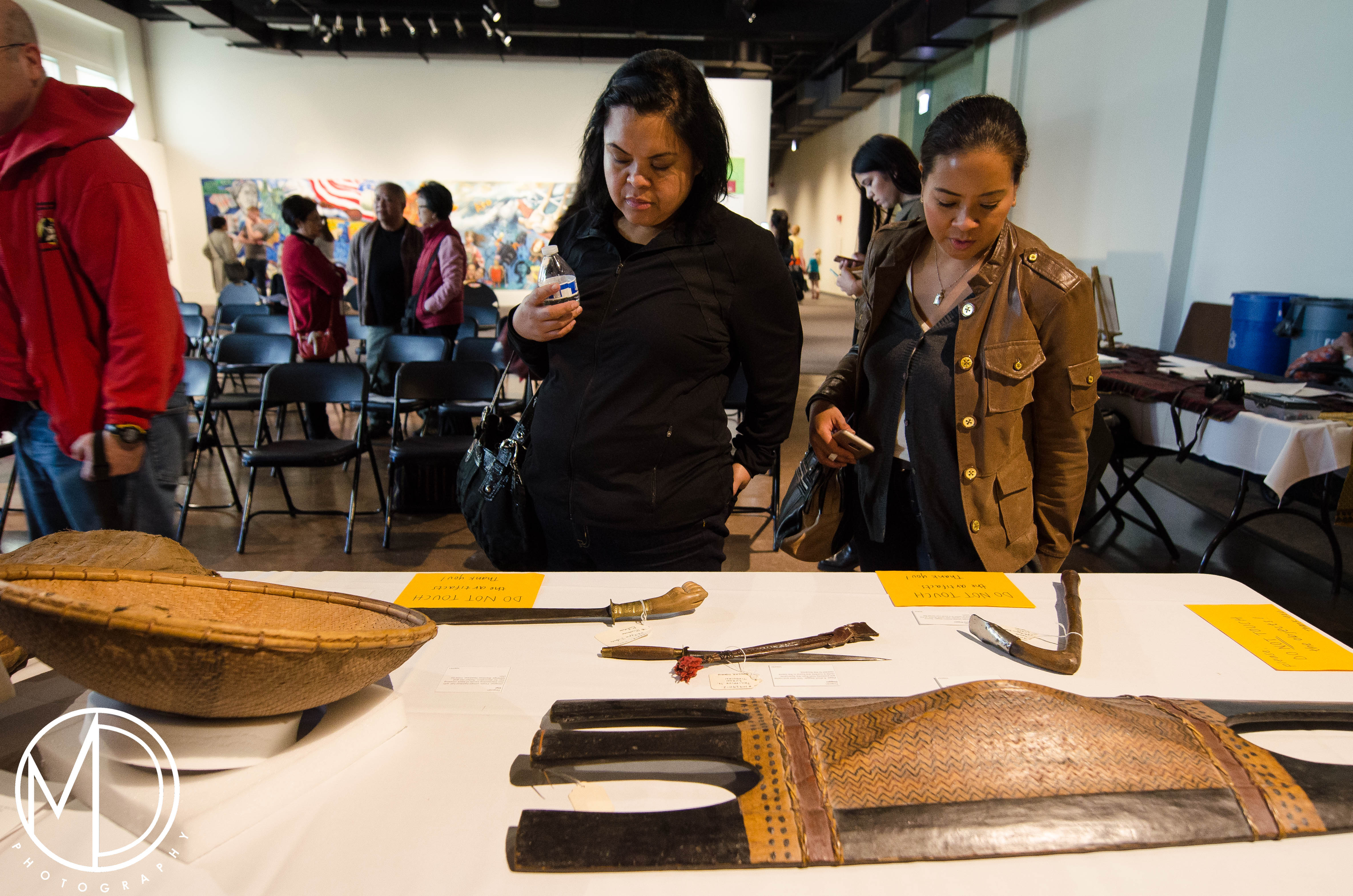 Guests looking at the blades and shields from the collection.