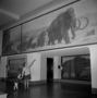 Rhoda Knight Kalt, and Melissa Kalt, daughter, granddaughter and great grand daughters of Charles Knight, visit Hall 38, underneath Mammoths and Cave Bear paintings by Knight. Titanotheres [Brontops] restorations by Frederick Blaschke in exhibit diorama case